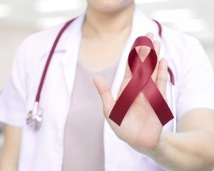 a woman holding a red ribbon for oral cancer awareness