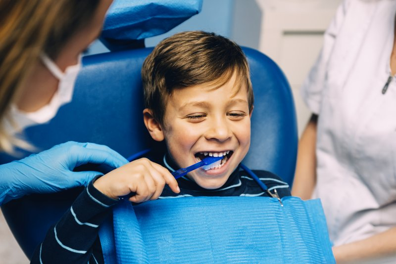 a little boy in the dentist chair using a manual brush to clean his teeth during his appointment