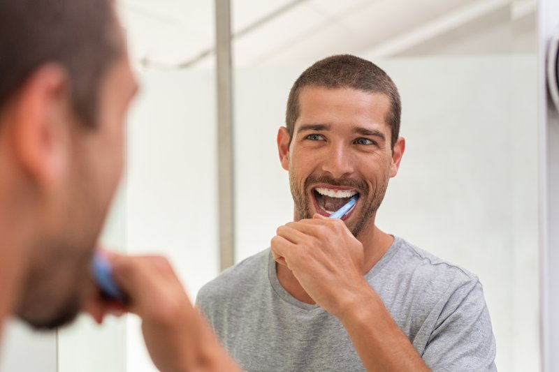 man brushing teeth before breakfast