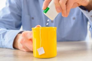 man pouring sugar substitutes into yellow coffee mug