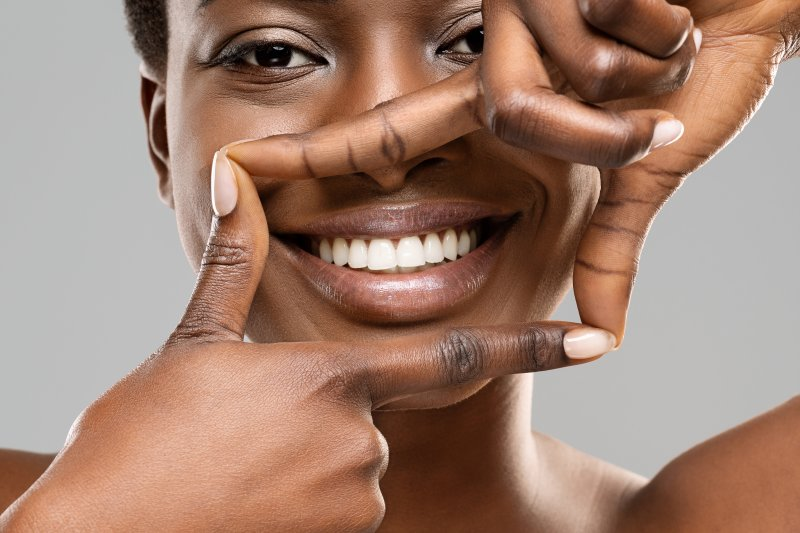 a young woman creating a box around her mouth with her fingers to show off her healthy smile